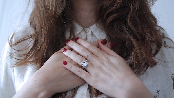 a woman holding her hands to the chest